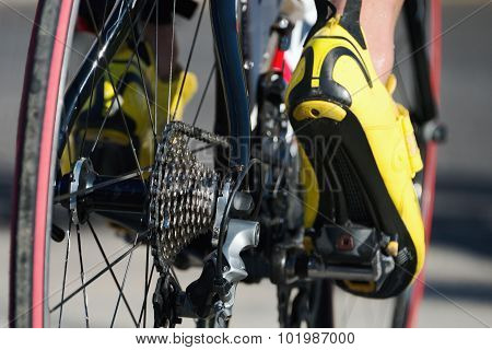 Cycling racing- bike detail on gear wheels and feet