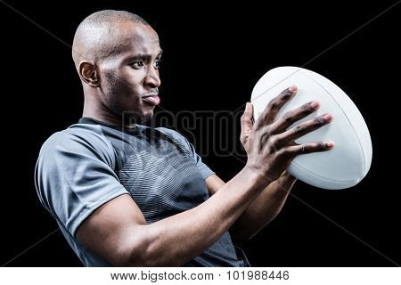 Rugby player looking away while throwing ball against black background