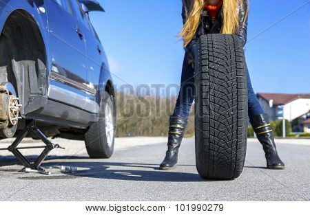Unexpected accident on the road Broken car suspended on the jackscrew, large wheel, female body behind that wheel poster