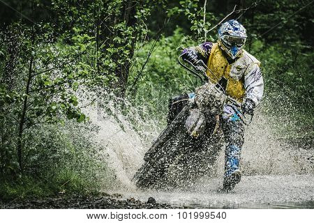 Motocross driver on wet and muddy terrain