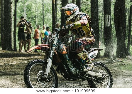 Motocross driver under the spray of water