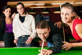 Group of four friends in a billiard hall playing snooker poster