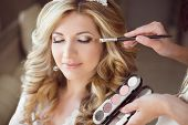Beautiful bride girl with wedding makeup and hairstyle. Stylist makes make-up bride on wedding day. portrait of young woman at morning. poster