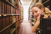 Portrait of cute girl sitting in wheelchair against close up of a bookshelf poster