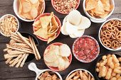 Salty crackers, tortilla chips and other savory snacks with salsa dip poster