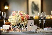 table setting for a wedding or dinner event very shallow depth of field with the focus on the flowers blurry background and blank name cards poster
