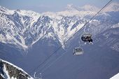 Skiers and snowboarders on a mountain ski lift poster