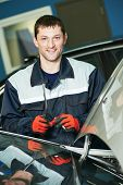 Portrait of automobile glazier repairman at windscreen or windshield of a car replacement in auto service station garage poster