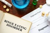 binge eating disorder written on book with tablets. Medicine concept. poster