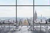 Workplaces in a modern panoramic office New York city view from the windows. Open space. Black tables and black leather chairs. A concept of financial consulting services. 3D rendering. poster