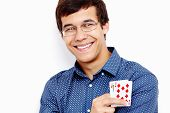 Close up portrait of young hispanic man wearing blue shirt and glasses holding Jack Ten in his hand and smiling against white wall - gambling concept poster