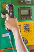 Hand holding handset of a public telephone background. poster