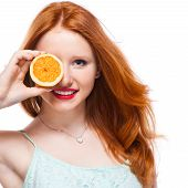 Beauty Model Girl takes Juicy Oranges. Beautiful Joyful teen girl with freckles funny red hairstyle yellow makeup and nails. Professional make up. Orange Slices. poster