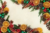 Christmas background border with dried fruit and spices, green bauble decorations, holly and winter greenery over old parchment paper. poster