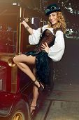 Beautiful elegant woman dressed in steampunk style posing over retro car poster