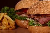 Few big tasty appetizing fresh burgers of green lettuce red tomato cheese bacon slice meat cutlet violet oinion white bread bun with sesame seeds and chips on wooden table closeup horizontal picture poster