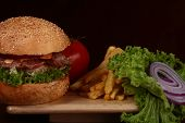 One big appetizing fresh burger of green lettuce red tomato cheese bacon slice meat cutlet onion and white bread bun with sesame seeds on wooden table on black background closeup horizontal photo poster
