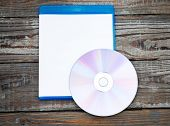 Blank compact disc with cover on wood background ground poster