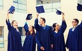 education, graduation and people concept - group of smiling students in gowns waving mortarboards outdoors poster