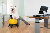 Young Happy Businesswoman Doing Fitness Exercise On Yellow Pilates Ball In Office poster