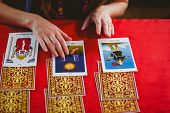 Fortune teller using tarot cards on red table poster