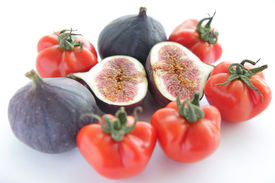 Figs and tomatoes for salad on white background