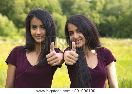 Portrait of a happy sisters twins showing thumbs up in summer. Outdoor shot Germany Hessen