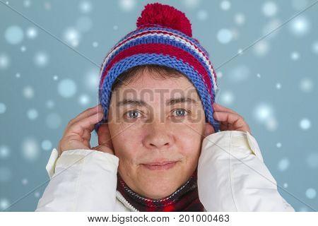 Woman is putting on winter cap. Shot in Studio.