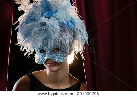 Portrait of woman wearing masquerade mask and wig in stage