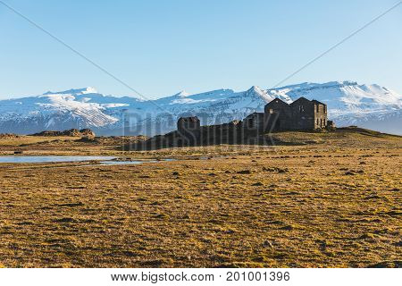 Iceland bleak landscape with ruined houses on foreground and snow covered mountains on background. Travel and winter concepts wild Icelandic place.