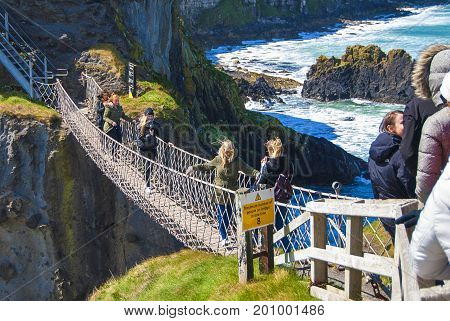 Ballintoy, United Kingdom - May 2, 2016: Carrick-a-Rede Rope Bridge, a popular tourist destination in Northern Ireland. Tourists passing the bridge.