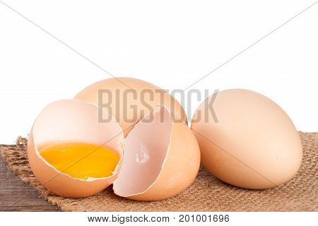 Broken egg with yolk and eggshell on a wooden table with a white background.