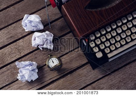 Overhead of vintage typewriter, pocket watch and crumbled paper on wooden table
