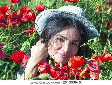 Portrait of beautiful brunette in a summer hat against a background of red poppies in the height of summer.Beautiful woman enjoying the bright red wild flowers, harmony concept.