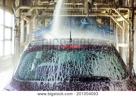 Car Wash, Black Car In Automatic Car Wash, Rotating Red And Blue Brush. Washing Vehicle.