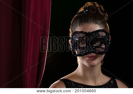 Portrait of woman wearing masquerade mask in stage