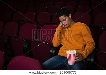Bored man with popcorn sleeping in theatre