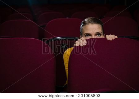 Woman scared while watching movie in theatre