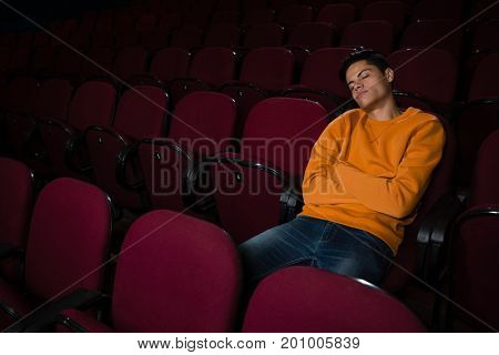 Bored man sleeping in the movie theatre
