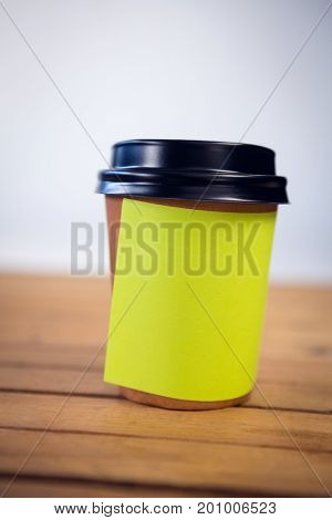 Close up of adhesive note stuck on disposable cup at table against wall