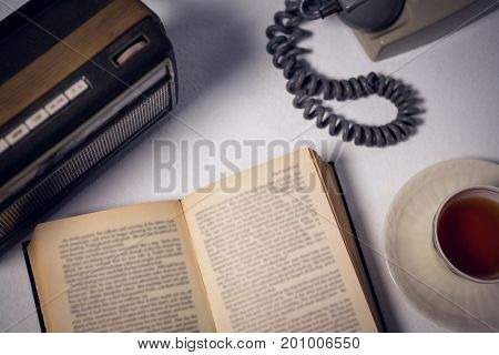 Overhead view of book with tea and telephone by radio on table