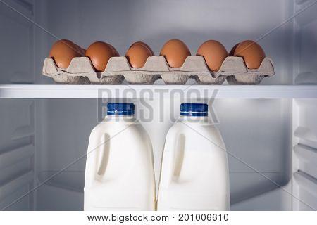 Egg carton and milk bottles in open refrigerator