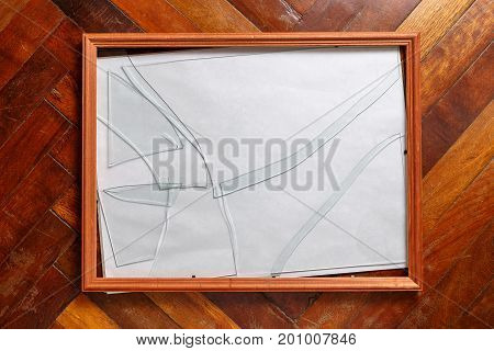 Wooden photo frame with broken glass lies on the floor
