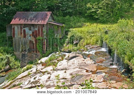 an old dilapidated gristmill at the bottom of a cascade
