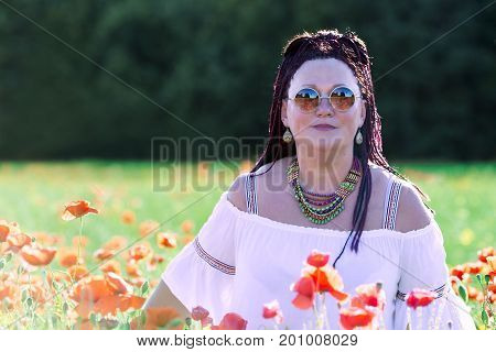 Portrait of beautiful woman with african pigtails against a background of red poppies in the height of summer. Beautiful woman enjoying the bright red wild flowers, harmony concept.