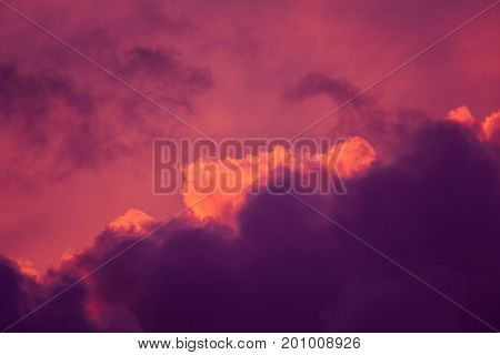 Magnificent colorful clouds in the evening sky. Bright pink clouds in the sky at sunset. Beautiful evening skyscape. Abstract purple pink background. Vibrant color photograph.