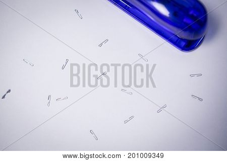 Overhead view of stapler by pins on white paper