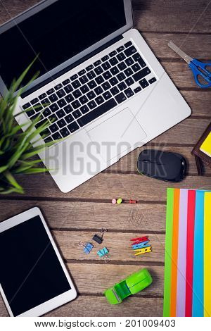 Overhead view of laptop and digital tablet with office supplies on wooden table