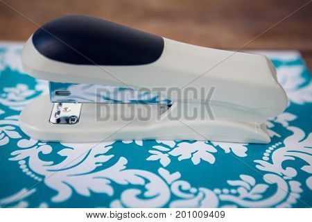 Close up of stapler on blue patterned paper at table