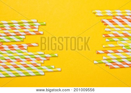 Colorful drinking straws on the yellow background
